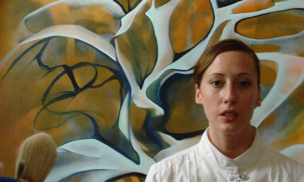 artist Megan Olson in front of her painting Untitled Orange